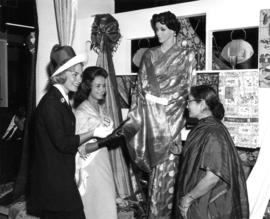 Beauty contestant and woman at Indian textile exhibit