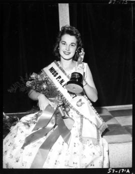 Carol Lucas, winner of Miss P.N.E. 1957, posing with flowers and trophy