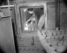 [Man stacking pottery pieces in a kiln]