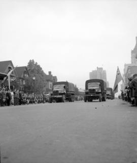 [Military vehicles passing by crowds during a military parade]