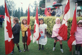 Five Brownies holding Canadian flags outside of Brockton Point Clubhouse