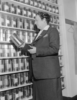 Mrs. Lillico [examining a tin of tea at] Empire Tea Bureau