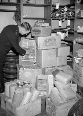 [Man in storeroom full of tea and coffee packages]
