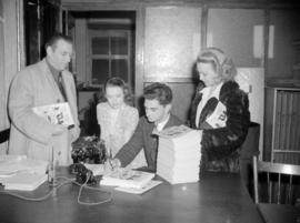 "[Columnist Jack Scott signing copies of ""Our Town""]"