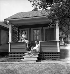 [Couple sitting on the steps of a small guest house on Bowen Island]