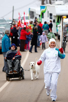 New Day 26 Torchbearer 54 Lucienne Donelle Easton runs the torch with son behind in Riverside-Alb...