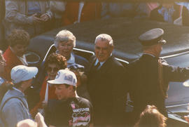 Crowd around Robert Gordon Rogers as he exits automobile