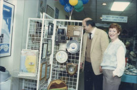 Mike Harcourt and unidentified woman in front of gift display