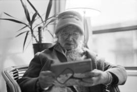 Lillian Ho Wong, age 89, looking at an object in a box