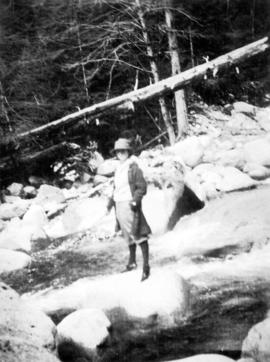 [Unidentified woman holding fishing rod while standing on large rock in river near Summit Lake]