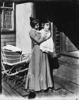 [Woman holding baby (Harold Timms) on porch of house]