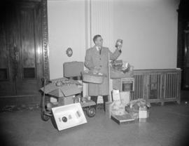 [Man posing with food and household products as part of the Vancouver Board of trade's 60th ...
