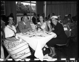 P.N.E. President W.J. Borrie sitting with Miss P.N.E. contestants and unidentified woman at tea p...