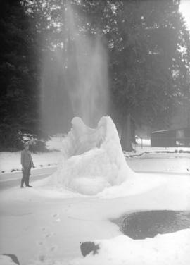[Man beside ice formation] frozen fountain in Stanley Park