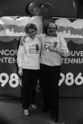 Unidentified man and woman wearing City of the Century sweatshirts in front of Centennial banner