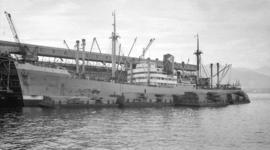 S.S. Kertosono [at dock, with lumber-filled barges alongside]