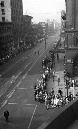 [Crowd gathered to watch parade along Georgia Street]