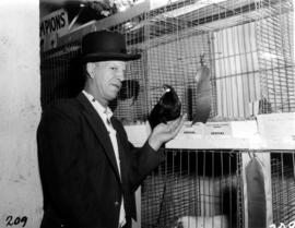 Man with award-winning bird in 1955 P.N.E. Poultry and Pet Stock competition