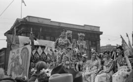 [Woman and men in costume on float in Chinese parade during VJ Day celebrations]