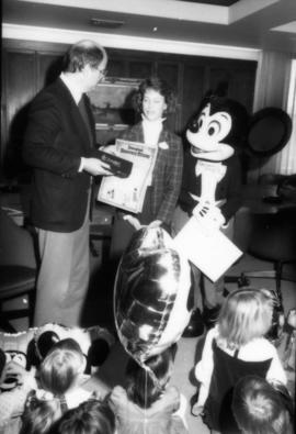 Mike Harcourt, Karen Neveu and Mickey Mouse standing in front of group of children