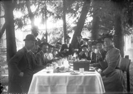 [Men and women assembled around a picnic table]