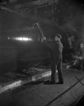 [Man painting or washing the exterior of a boiler at Vancouver Iron Works Ltd.]