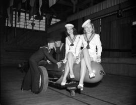 [Two women in sailor suits sitting on a torpedo being pushed by two sailors at HMCS Discovery as ...