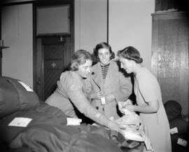 [Women checking Red Cross supplies]