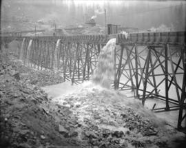 [Partially constructed Coquitlam Dam, showing the sluicing of material from the adjacent borrow pit]