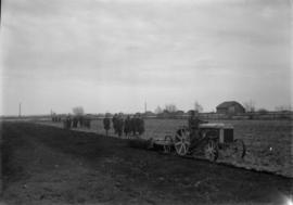 Man on tractor tilling a field with men walking behind