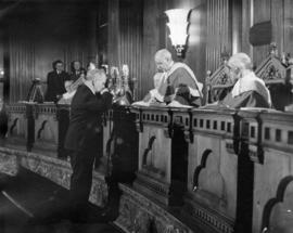 Courtroom scene with five justices and a man taking oath before them