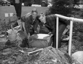 Putting time capsule into hole to be covered with Centuries Rock, Queen Elizabeth Park