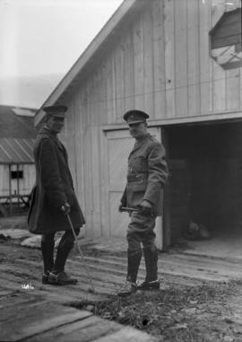 [Two soldiers in front of a barn]