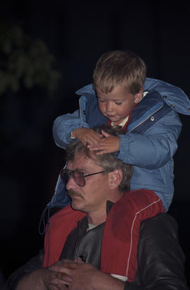 Boy sitting on mans shoulders at the lighting of the Peace Flame Monument ceremony