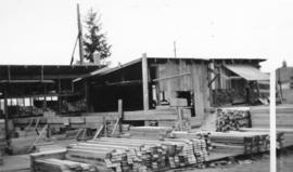 [Exterior of a temporary woodworkers' shop showing precut lumber in King's Lynn]