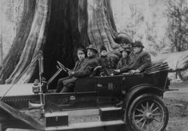 [Family in touring car parked at the Hollow Tree in Stanley Park]