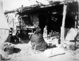 [First Nations woman and child sitting outside of house]