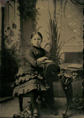 [Studio portrait of girl, seated]
