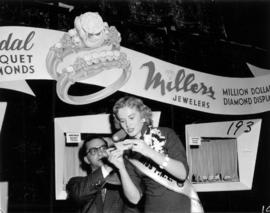 Miss P.N.E., Glenda Sjoberg, announces winning ticket at Millers Jewelers display in Manufacturer...