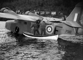 [Men in a boat pushing on the side of a military seaplane]