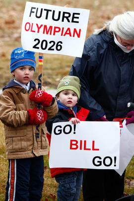 New Day 27 Boys cheer on the flame with signs as it passes in New Brunswick.