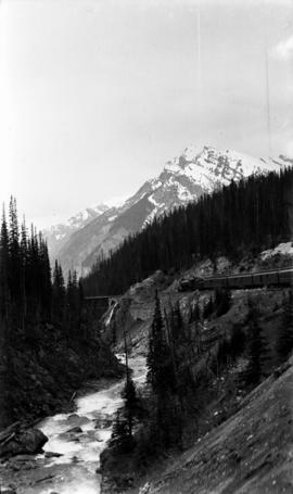 [View] from train in Rockies [of a train approaching a bridge]