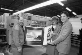 Toni Onley, unidentified woman and Robert Dubberley hold up Centennial Art Series print