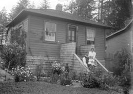 [Man, woman and child seated on front steps of house in Grandview-Cedar Cottage area]