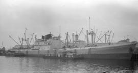 "M.S. Wokingham [at dock, at Pier ""B"", with lumber-filled barges alongside]"