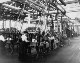 Interior of cannery with women and children working at machines