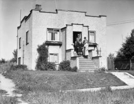 Four people standing on the steps of a stuccoed  Vancouver house