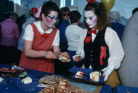 Women in face paint and costumes serving Vancouver's 99th birthday cake
