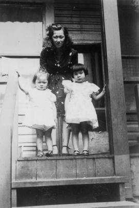 Woman and two children on steps of house