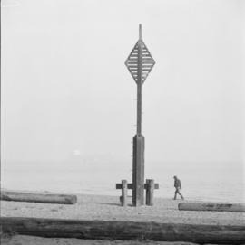 [Man walking along shore at] Spanish Banks